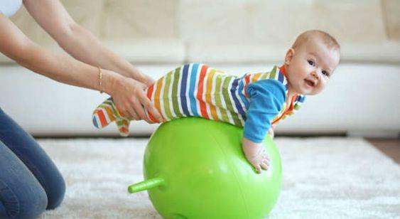 Bebé sobre una pelota inflada divirtiéndose